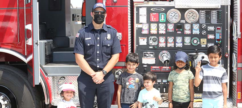 Firefighter taking picture with kids in front of the firetruck